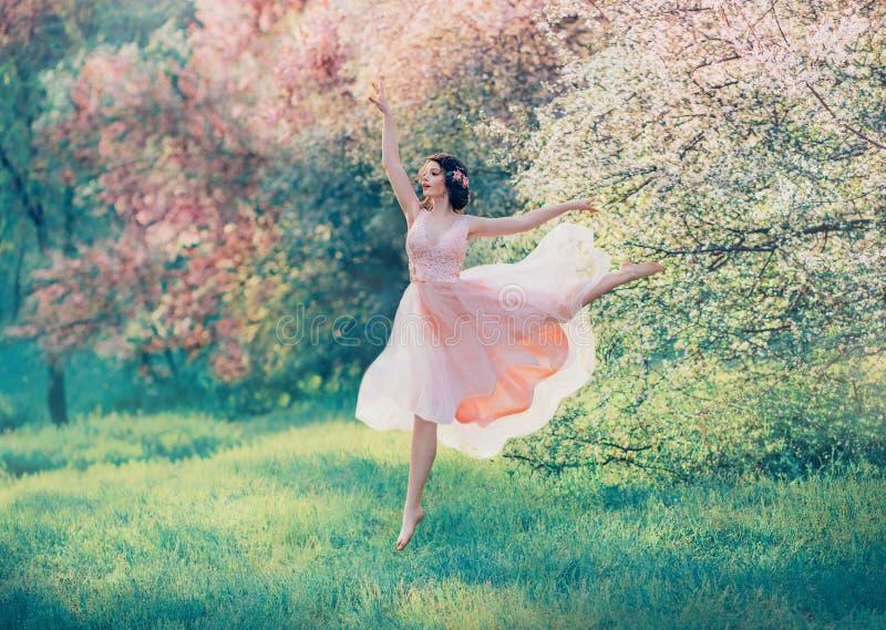 在飞行桃红色礼服跳舞的复兴的瓷玩偶在开花的春天森林,有黑发的嫩夫人里在明亮 免版税库存图片