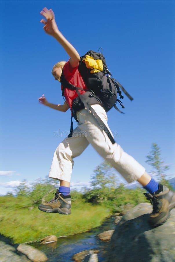 在飞跃河佩带的妇女年轻人的背包间 库存图片