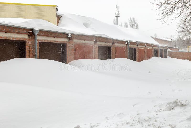 在飞雪期间,巨大的雪在车库门附近开户在冬天 图库摄影