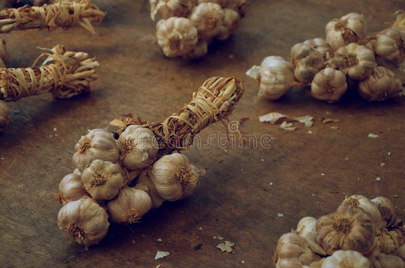 在食物市场,木背景,看法的关闭上的大蒜串 图库摄影