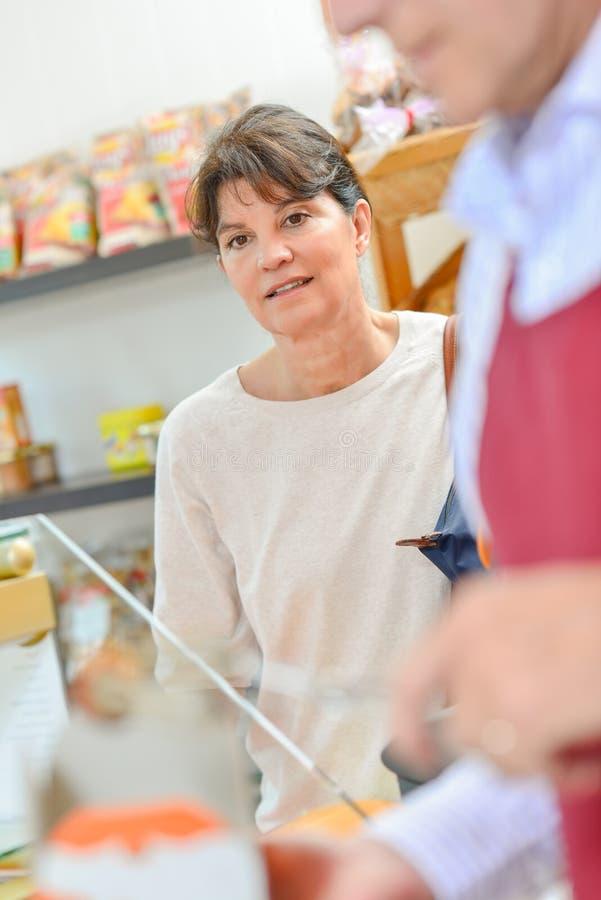 在食物店担任的女性顾客 图库摄影