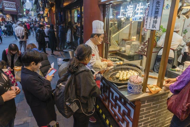 在食物摊位的人买的平底锅油煎的上海饺子 免版税库存图片