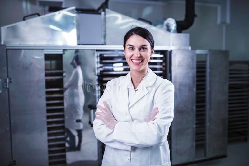 在食物烘干机脱水剂机器前面的微笑的女性工程师 库存照片