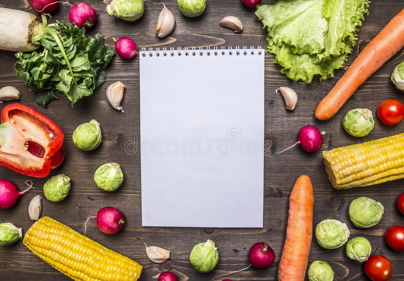 在食谱的一个笔记本附近被计划的新鲜蔬菜和草本在边界,地方的木土气背景顶视图关闭为 免版税库存图片