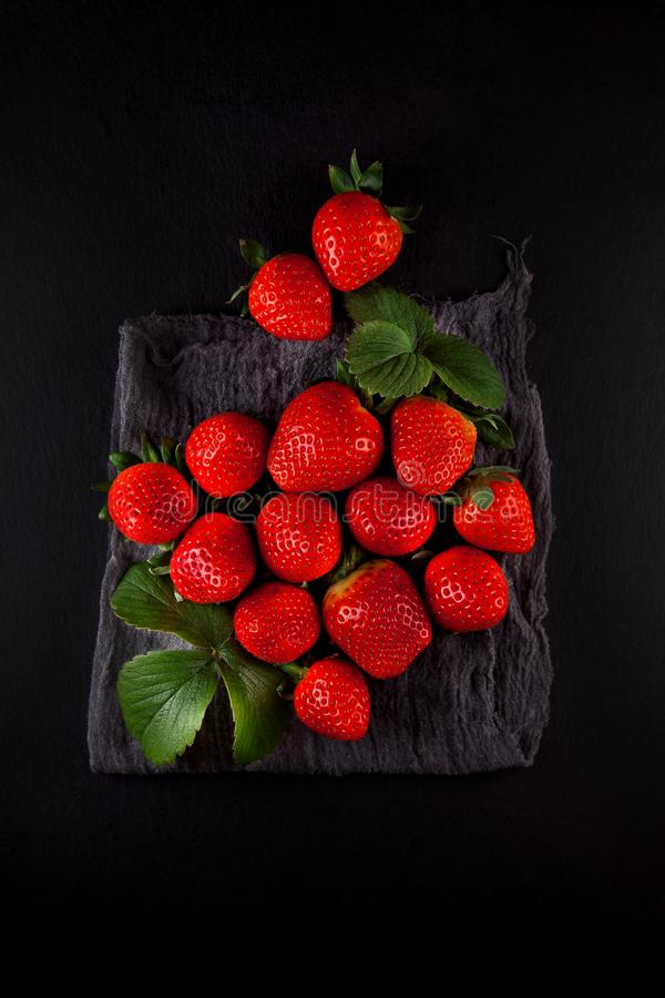 在餐巾和板岩的新鲜的成熟草莓镀厨房用桌 免版税库存图片