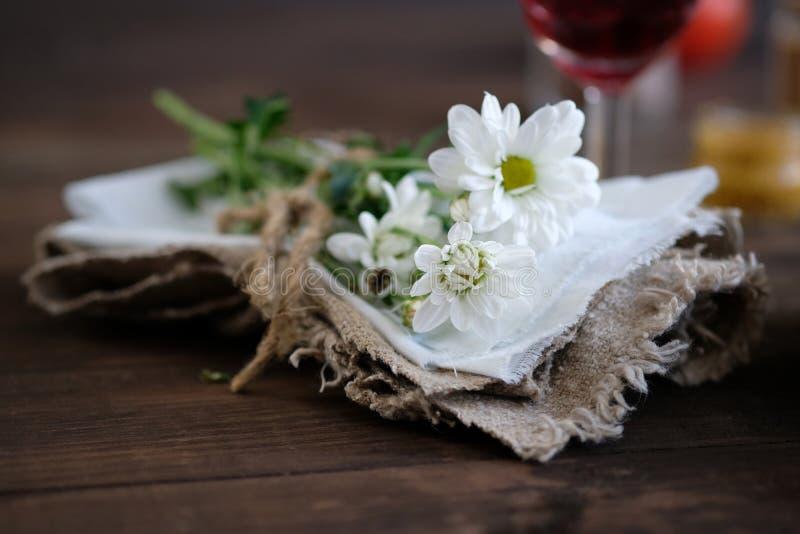 在餐巾的春黄菊在老木桌上 免版税库存图片