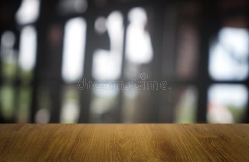 在餐馆、咖啡馆和咖啡馆内部前面抽象被弄脏的背景的空的黑暗的木桌  能使用为 免版税库存图片