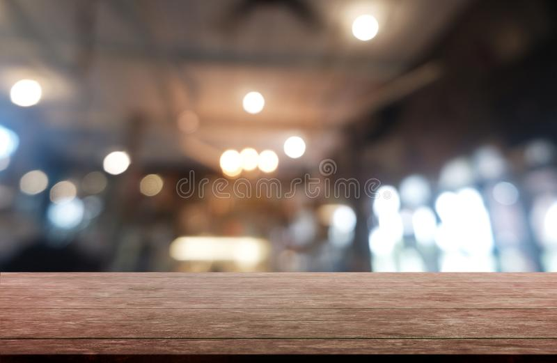 在餐馆、咖啡馆和咖啡馆内部前面抽象被弄脏的背景的空的黑暗的木桌  能使用为 库存照片