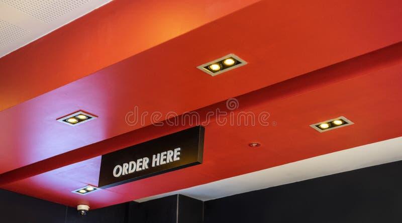 在餐馆、商店,办公室或者其他里面的这里命令标志 库存图片