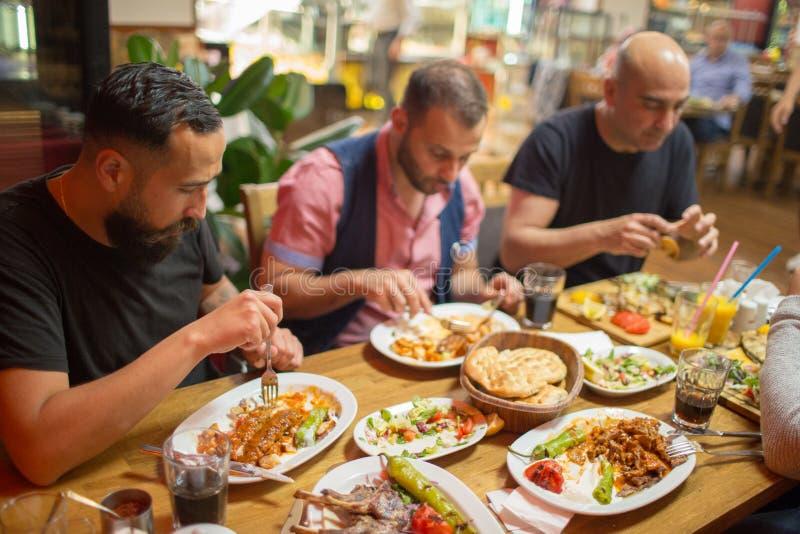 在餐馆享用中东食物的阿拉伯人 库存照片