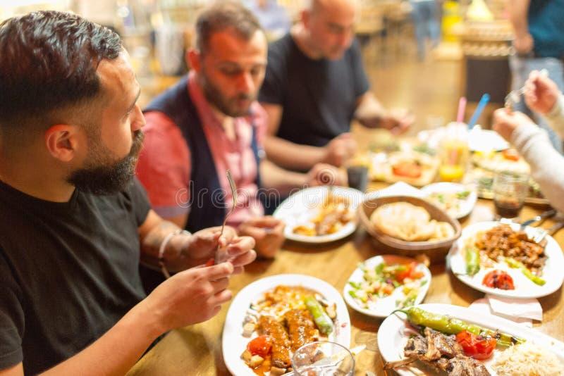 在餐馆享用中东食物的阿拉伯人 免版税库存照片