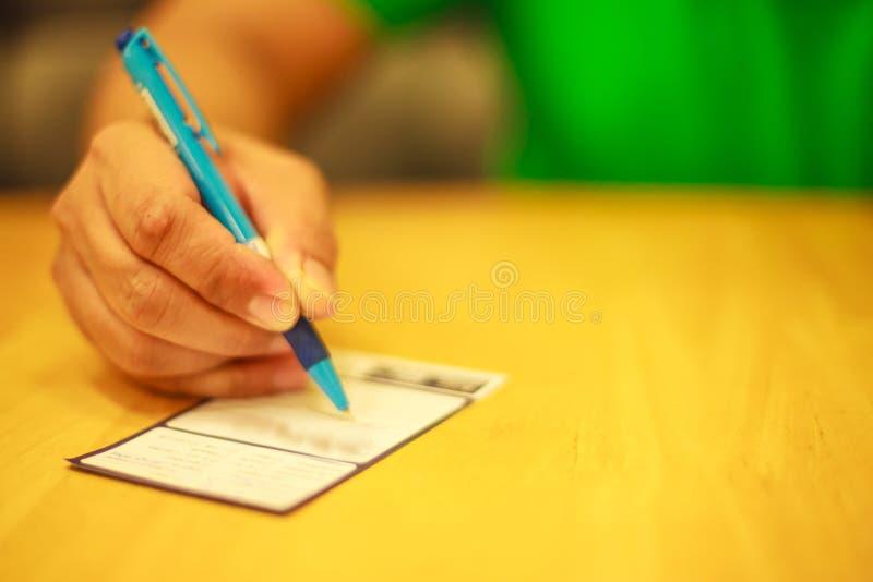在餐馆供以人员在幸运的凹道优惠券、备忘录、评论、建议或者查询表的` s右手文字在木桌上 库存照片