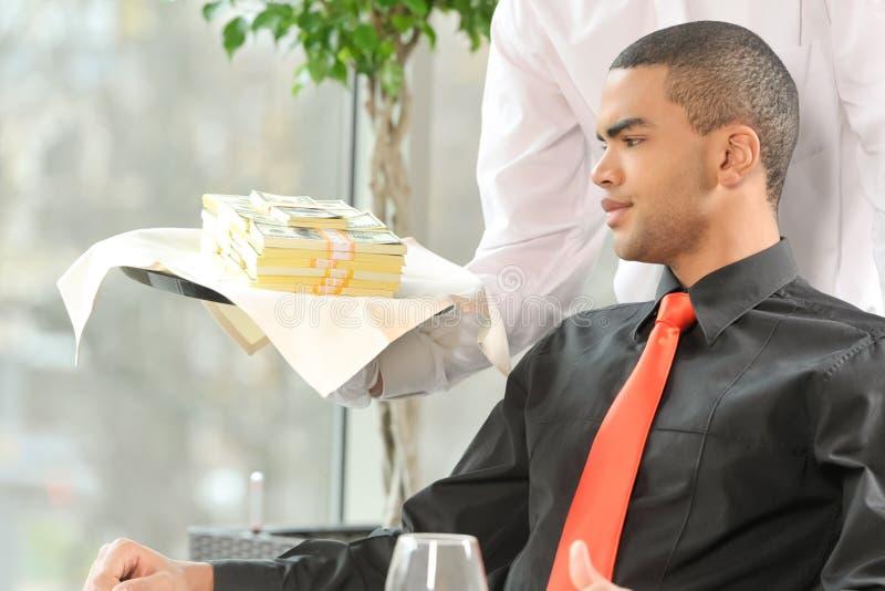 在餐馆供以人员坐和看金钱 库存图片