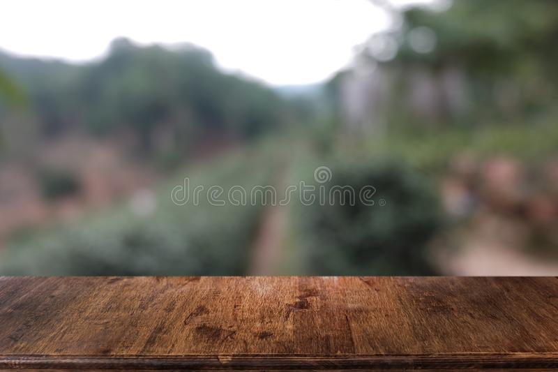 在餐馆前面抽象被弄脏的bokeh背景的空的黑暗的木桌  免版税库存图片