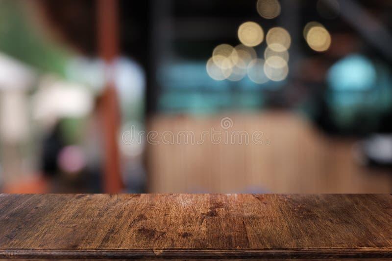 在餐馆前面抽象被弄脏的bokeh背景的空的黑暗的木桌  库存照片