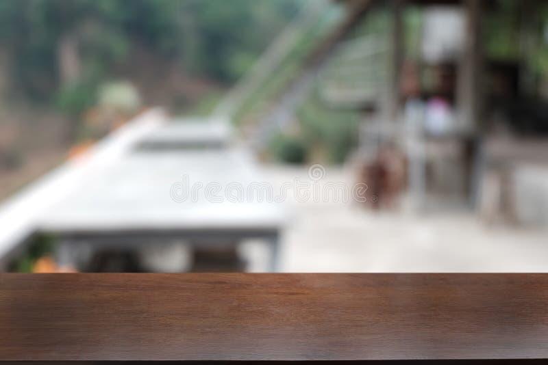 在餐馆前面抽象被弄脏的bokeh背景的空的黑暗的木桌  库存图片