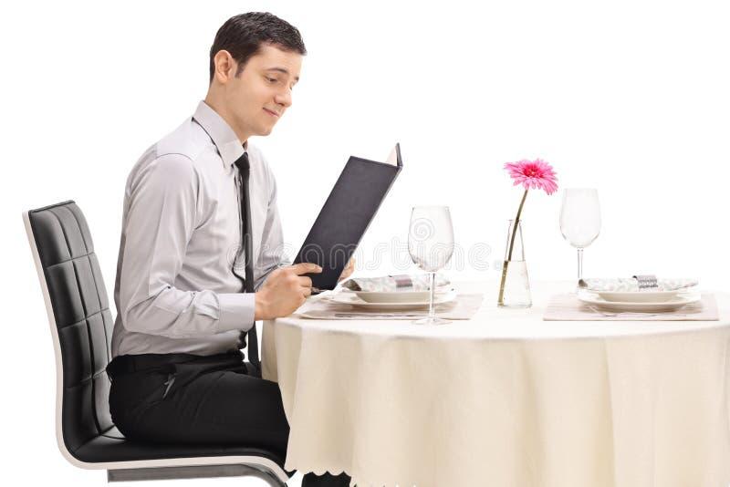 在餐馆桌上读菜单的年轻人 免版税库存图片