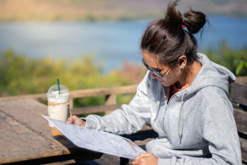 在餐馆的亚洲美女读书菜单有在桌上的咖啡杯的 免版税库存照片