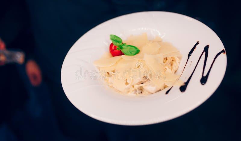 在餐馆的侍者服务的面团意粉沙拉点缀,接近看法 吃和休闲概念 被定调子的图象 有选择性的focu 免版税库存照片