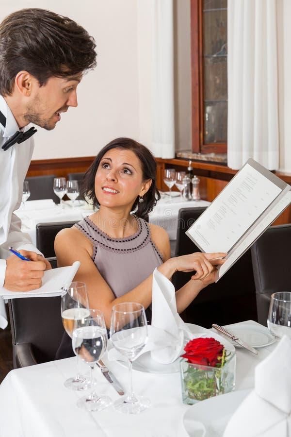 在餐馆的年轻微笑的夫妇 免版税库存照片