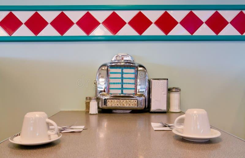 在餐馆表1950样式的自动电唱机。 免版税库存照片