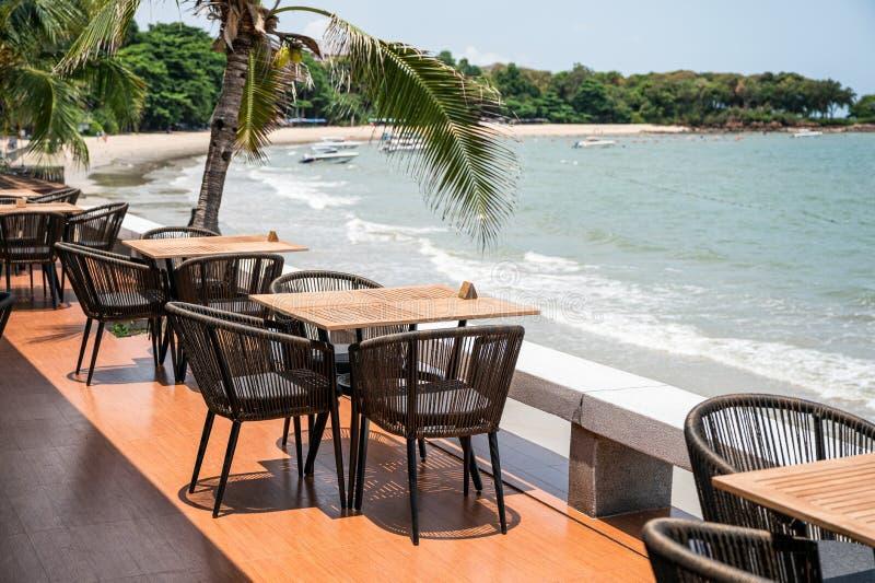 在餐馆露台的木饭桌在海边 库存照片