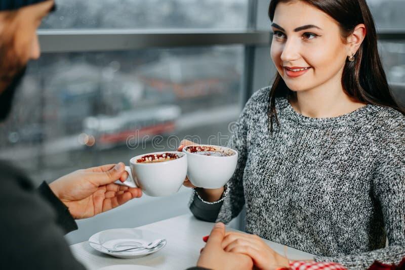 在餐馆,饮用的咖啡的愉快的年轻夫妇约会 Valent 免版税库存照片
