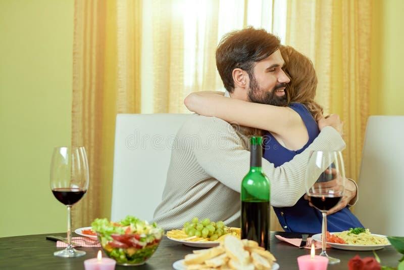 在饭桌拥抱的夫妇 免版税库存照片