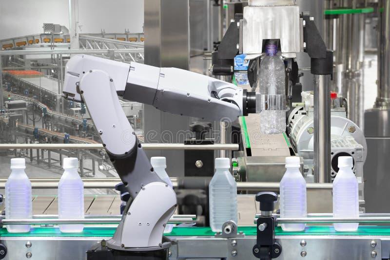 在饮料生产线的机器人武器储备水瓶 免版税库存图片