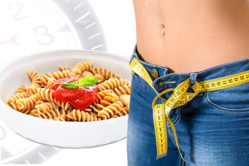 在饮食和食物背景以后的女孩佩带的牛仔裤 免版税库存图片