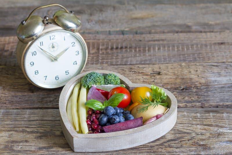 在饮食概念的时间与闹钟和健康食物在心脏 免版税库存图片