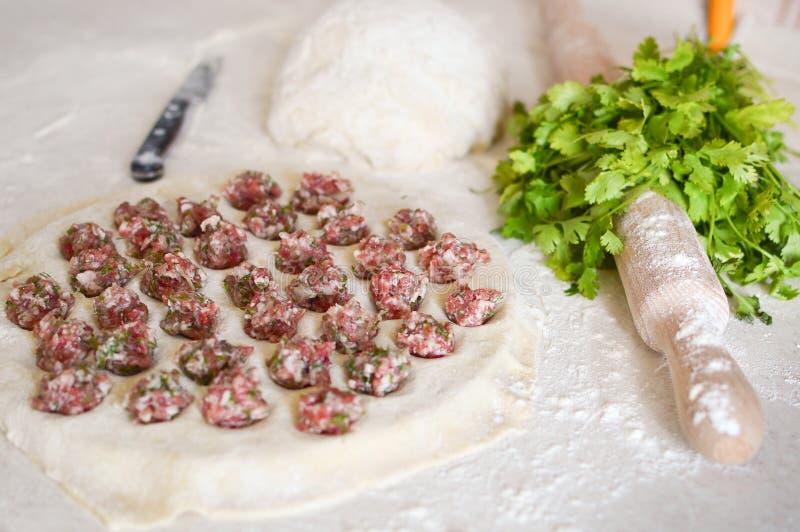 在饺子的自创饺子 饺子用在一张桌上的肉末用面粉 r 库存图片