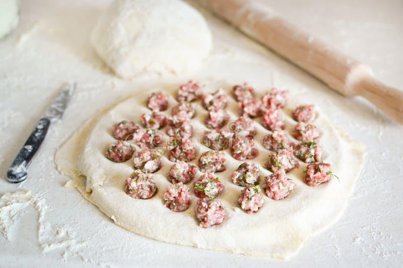 在饺子的自创饺子 饺子用在一张桌上的肉末用面粉 r 库存照片