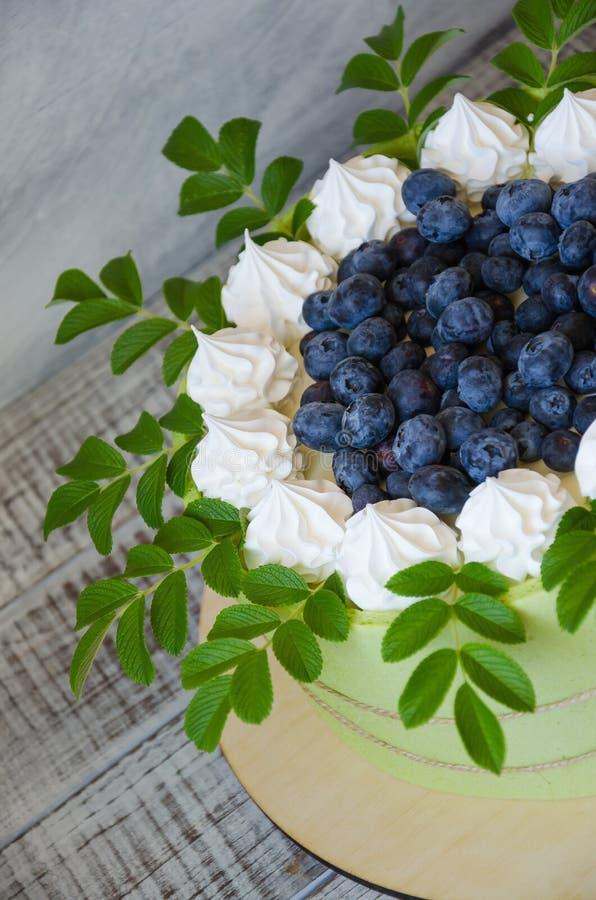 在饼干磁带包裹的生日蛋糕用蓝莓和meren 库存照片