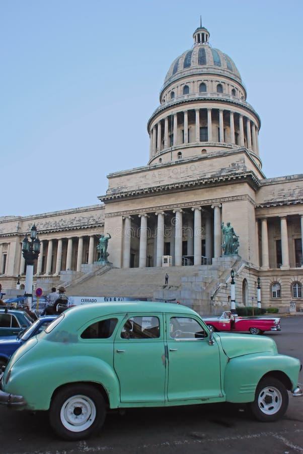 在首都大厦前面的老绿色古巴汽车 免版税库存图片