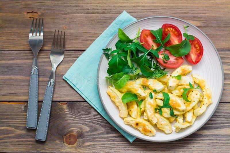 在香料夏南瓜烘烤的切片用在一块板材的在一张木桌上的乳酪用蕃茄和芝麻菜和叉子 库存照片