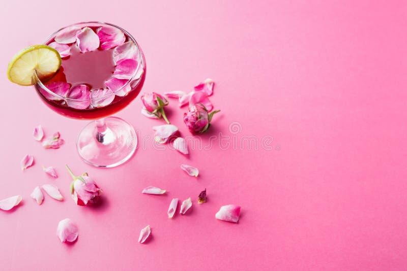 在香槟玻璃的罗斯鸡尾酒在桃红色背景 免版税库存图片
