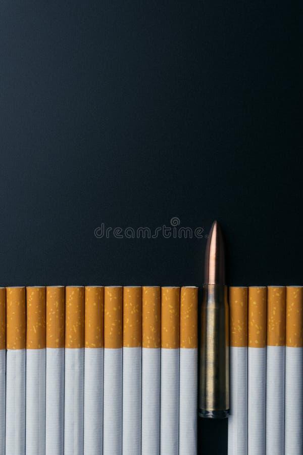 在香烟中的一枚枪子弹在黑暗的背景 库存图片