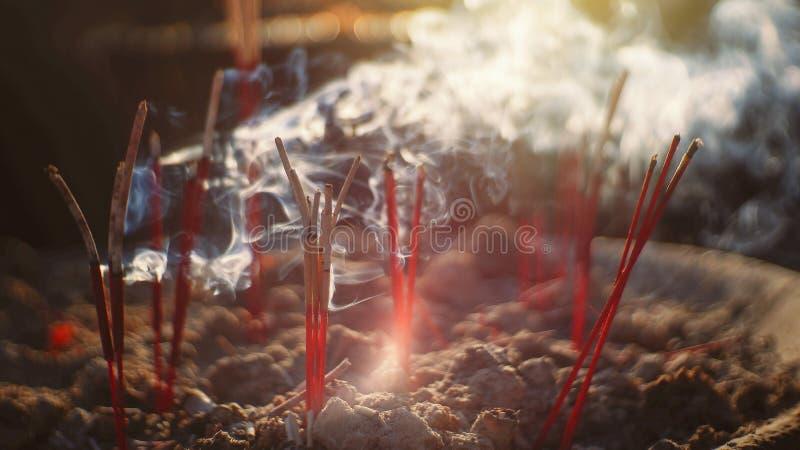 在香罐的香火棍子烧和薪水尊敬的对菩萨,在香的选择聚焦很多烟用途 库存图片