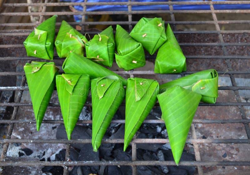 在香蕉叶子的烤甜黏米饭在木炭火炉 免版税库存照片