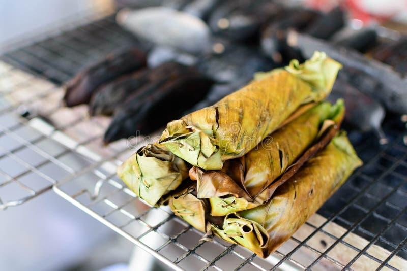 在香蕉叶子的烤黏米饭在火炉选择聚焦 免版税图库摄影