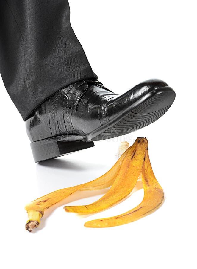 在香蕉果皮的生意人英尺 免版税图库摄影