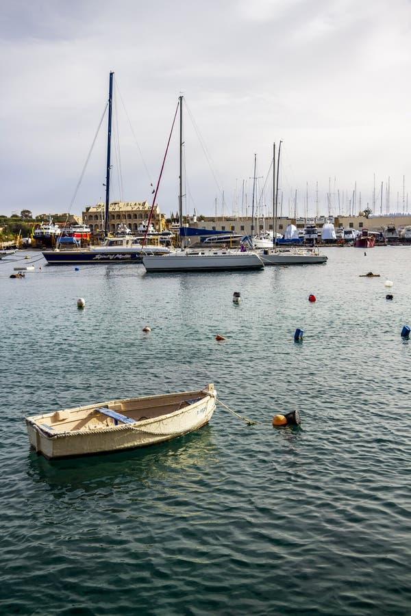 在马努埃尔海岛游艇围场的一条老木白色小船在Gzira,马耳他,小船的各种各样的类型在背景中 库存图片