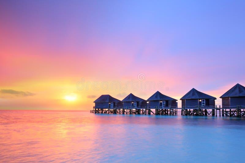 在马尔代夫海岛,水别墅上的日落依靠 免版税库存图片
