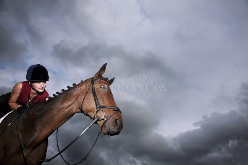 在马的女性骑师骑马 免版税库存图片