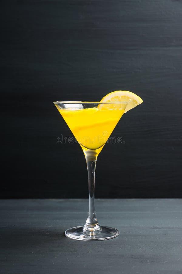 在马蒂尼鸡尾酒玻璃的新鲜的柠檬鸡尾酒在木背景 免版税库存图片