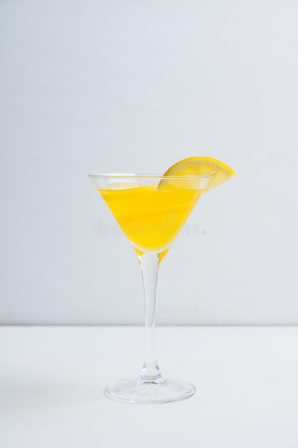 在马蒂尼鸡尾酒玻璃的新鲜的柠檬鸡尾酒在木背景 免版税图库摄影