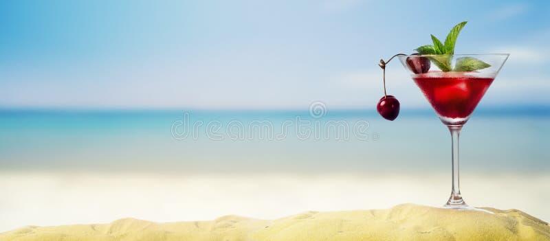 在马蒂尼鸡尾酒玻璃的樱桃鸡尾酒在热带沙滩 库存图片
