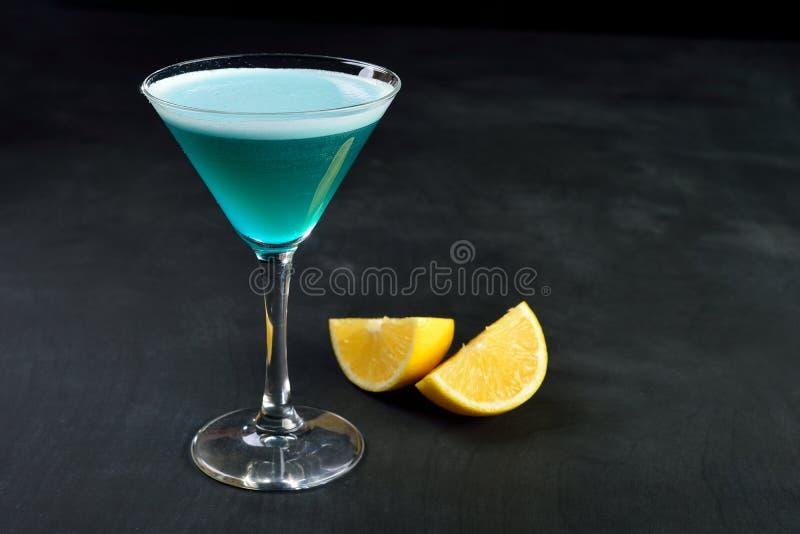 在马蒂尼鸡尾酒玻璃的蓝色冷的鸡尾酒有柠檬黑暗的背景 免版税图库摄影