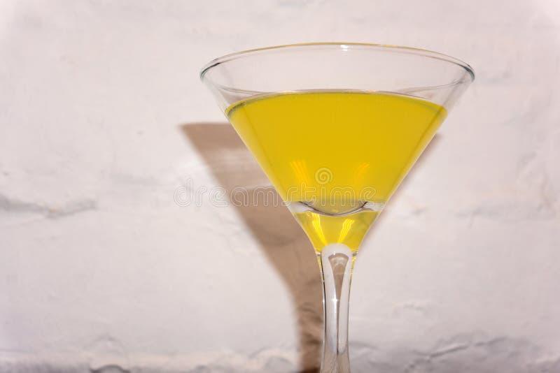 在马蒂尼鸡尾酒玻璃的黄色鸡尾酒在白色背景 免版税库存图片